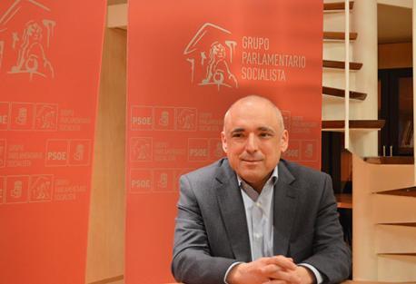 El político Rafael Simancas sentado en una sala con carteles del PSOE