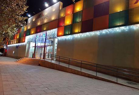 Entrada principal del centro comercial Vicálvaro, situado en el distrito del mismo nombre. La foto fue tomada de noche y la fachada está decorada con luces.