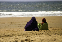 Dos mujeres con velo sentadas en la playa de Mazagón en España