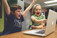 Niño y niña jugando con un portátil